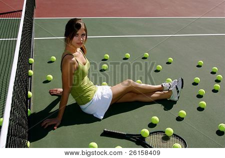 Brunette woman on the tennis court surrounded by tennis balls