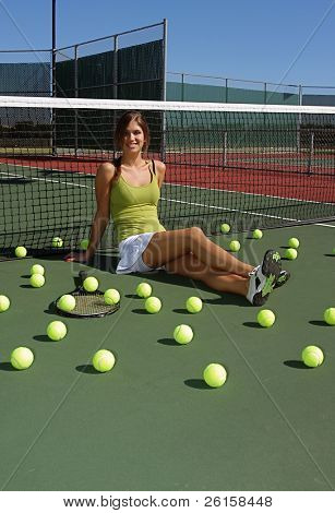 Brunette female tennis player surrounded by tennis balls