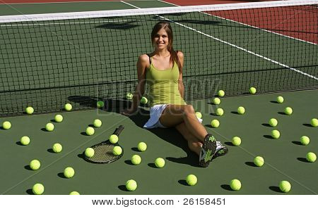 Brunette tennis girl on the court surrounded by tennis balls