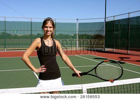 Brunette female tennis player holding her racket