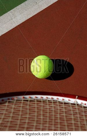 Tennis ball on the court with racquet in the forefront, room for copy