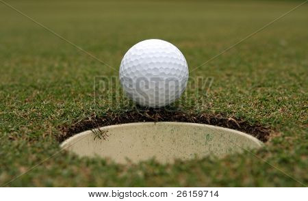 Golf ball on the lip of the cup