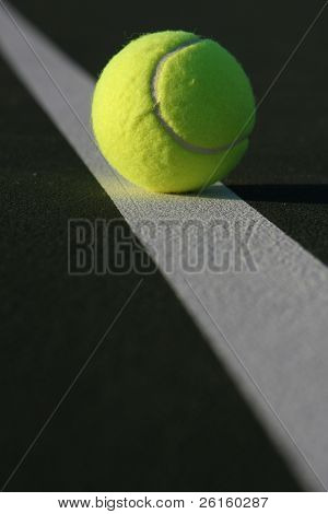 Tennis ball on a court line with room for copy in the foreground