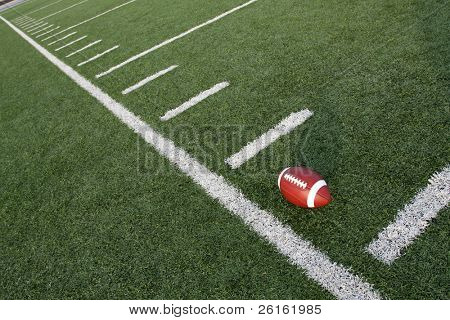 American Football near the yard lines of a field angled for effect