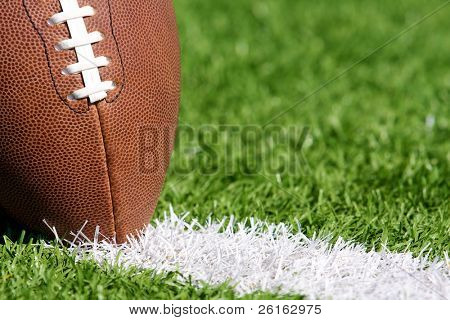 Close up of a Pro Football on the Yard Line of a Field with shallow depth of field and room for copy