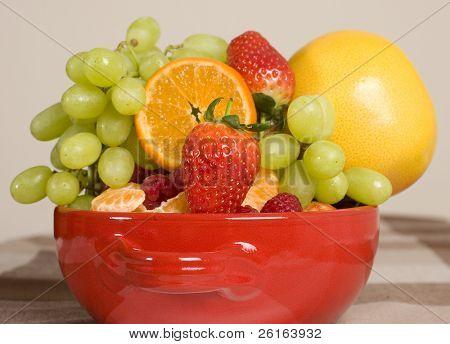 Bol rojo lleno de frutas mezcladas, saludables dieta alternativa fuente natural de vitaminas
