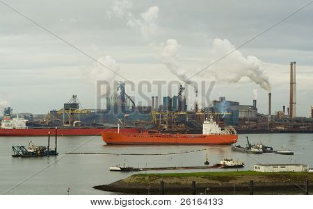 2 large ships in harbor, oil refinery in background, heavy industry pollution