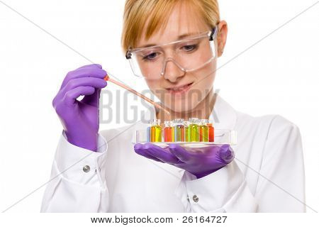 female researcher doing some experiment, holds a tray with small test tubes filled with different chemicals and working with pipette filled with red one, studio shoot isolated on white