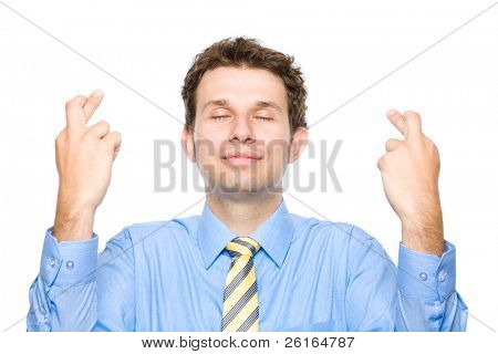 young attractive male holds his fingers crossed and eyes closed, wishful thinking, studio shoot isolated on white background