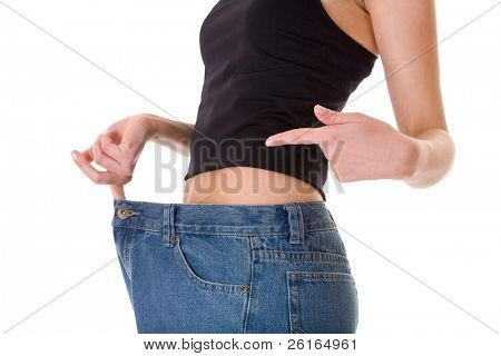 attractive and young female shows her old huge pair of jeans, weight loss concept, studio shoot isolated on white