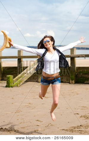 young attractive female jump high over sandy summer, wears sunglasses and holds straw hat in her hand