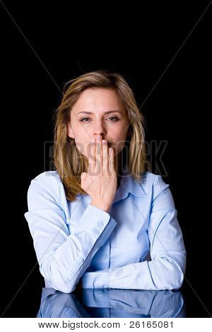 attractive blonde female cover her mouth with her hand, secrecy concept, studio shoot isolated on black