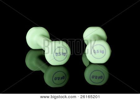 pair of green half kilo dumbbells, studio shoot isolated on black with reflection