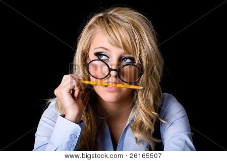 young attractive blonde female in geek glasses, eats yellow pencil, stress, pressure concept, studio shoot isolated on black