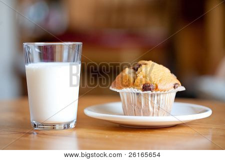 chocolate muffin with chocolate chips and full glass of milk