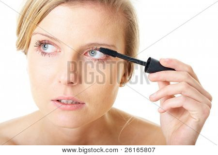 blonde female with mascara brush, morning make up, studio shoot isolated on white