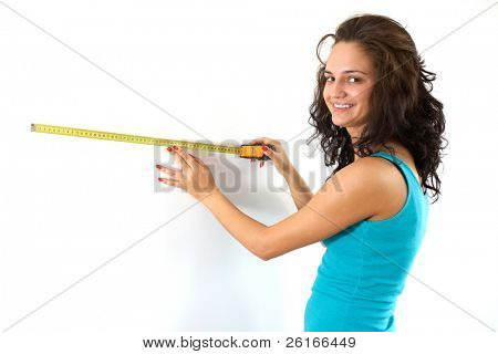 young attractive brunette female measure white wall