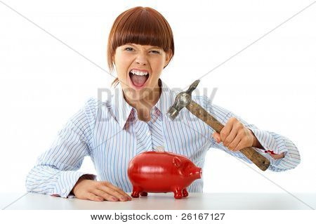 young redhead female trying to break into red piggy bank, spending your savings concept, isolated on white