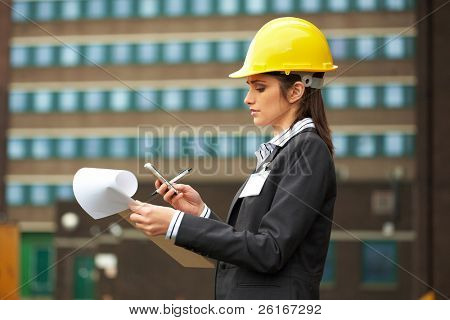 young female architect in yellow hard hat check her mobile phone, construction site
