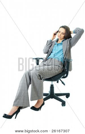 businesswoman in blue shirt and suit sits on office chair and talks over mobile phone, isolated on white