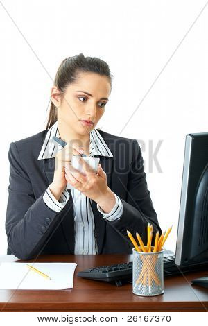 attractive female in suit and shirt make notes, copy something from computer screen in front of her, isolated on white