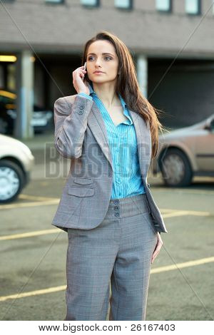 young very attractive businesswoman talks over her mobile phone, blurred cars as background, outdoor shoot