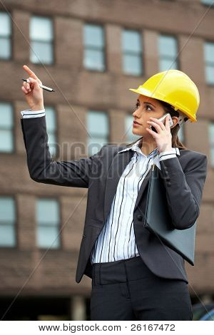 young female architect in hard hat talks over mobile phone and point to the building in front of her
