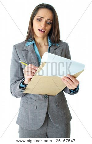 young attractive but shocked businesswoman makes some notes or calculation with pencil and paper on wooden board, isolated on white, foreground focus