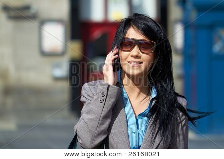 young attractive businesswoman talks over mobile phone, outdoor shoot
