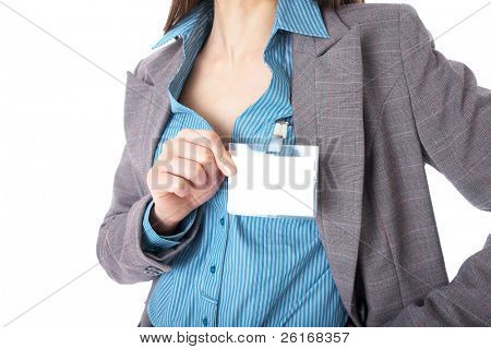 female hand holds blank name badge, wears blue shirt and grey suit