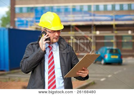 young architect or inspector talk over his mobile phone, outdoor shoot with blurred office building as background