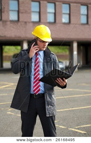 young architect or inspector with office building as blurred background, talks over his mobile phone