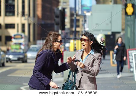 two happy females laugh and have good time together, elegant business look, wears coat and suit with shirt, background is blurred