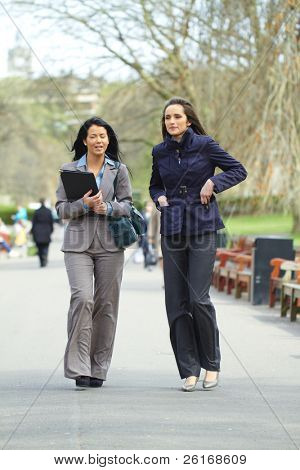 two attractive businesswoman walk in the park, both wear shirt and suit, elegant look, outdoor shoot