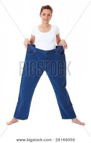 attractive and young female shows her old huge pair of jeans, weight loss concept, studio shoot
