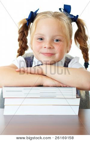 Blonde happy schoolgirl in blue dress and matching tie sits at her school desk with pile of books in front of her, isolated on white