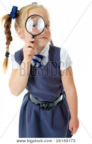 Blonde happy curious schoolgirl in blue dress and matching tie isolated on white holds magnifying glass