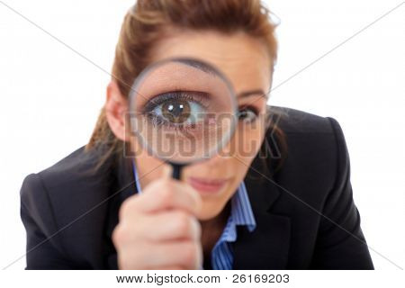 Attractive businesswoman holds magnifying glass, search or spy concept, isolated on white