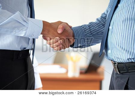 two male hands in business handshake, both wear blue shirts