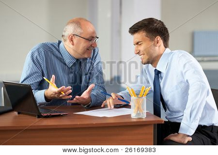 senior and junior businessman discuss something during their meeting, joking about somethign and both laugh, office background