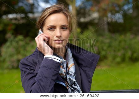 Portrait of attractive businesswoman talking over her mobile phone, outdoor park shoot