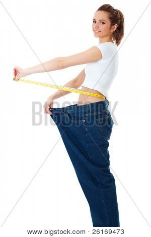 Attractive young woman shows her old huge jeans, successful dieting concept, isolated on white