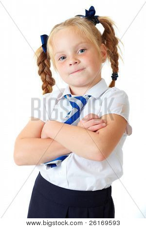 Blonde happy schoolgirl in blue dress and pigtails with crossed arms, shoot over white background.