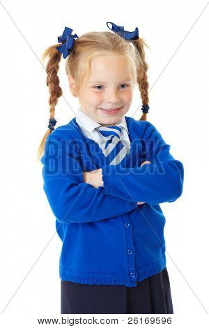 Blonde happy schoolgirl in blue dress and pigtails with crossed arms, isolated on white.