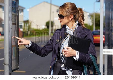 Attractive and trendy businesswoman wait for bus, check bus time on bus stop timetable, street shoot