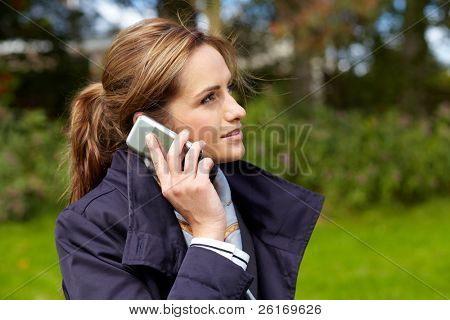 Portrait of attractive businesswoman talking over her mobile phone, outdoor park shoot