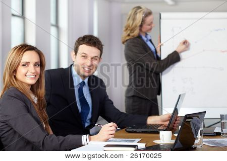 Business meeting, two colleagues on foreground while blonde female presents graph on flipchart on the background