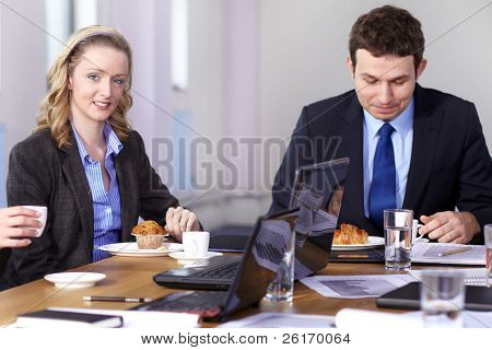 Young businessman and businesswoman sitting at conference table have a break during meeting