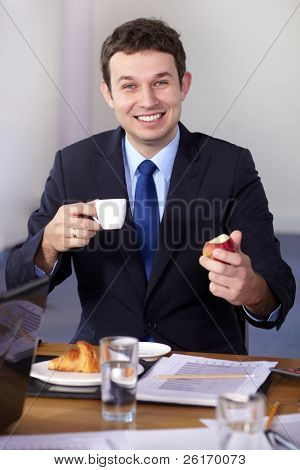 Young businessman sitting at conference table have a break during meeting, holds coffee cup and apple