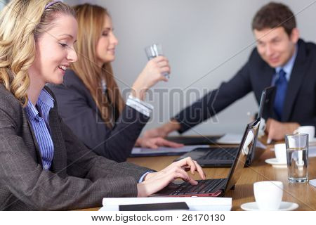 Team of 3 business people during meeting, sitting at big conference table. One female works on her laptop.